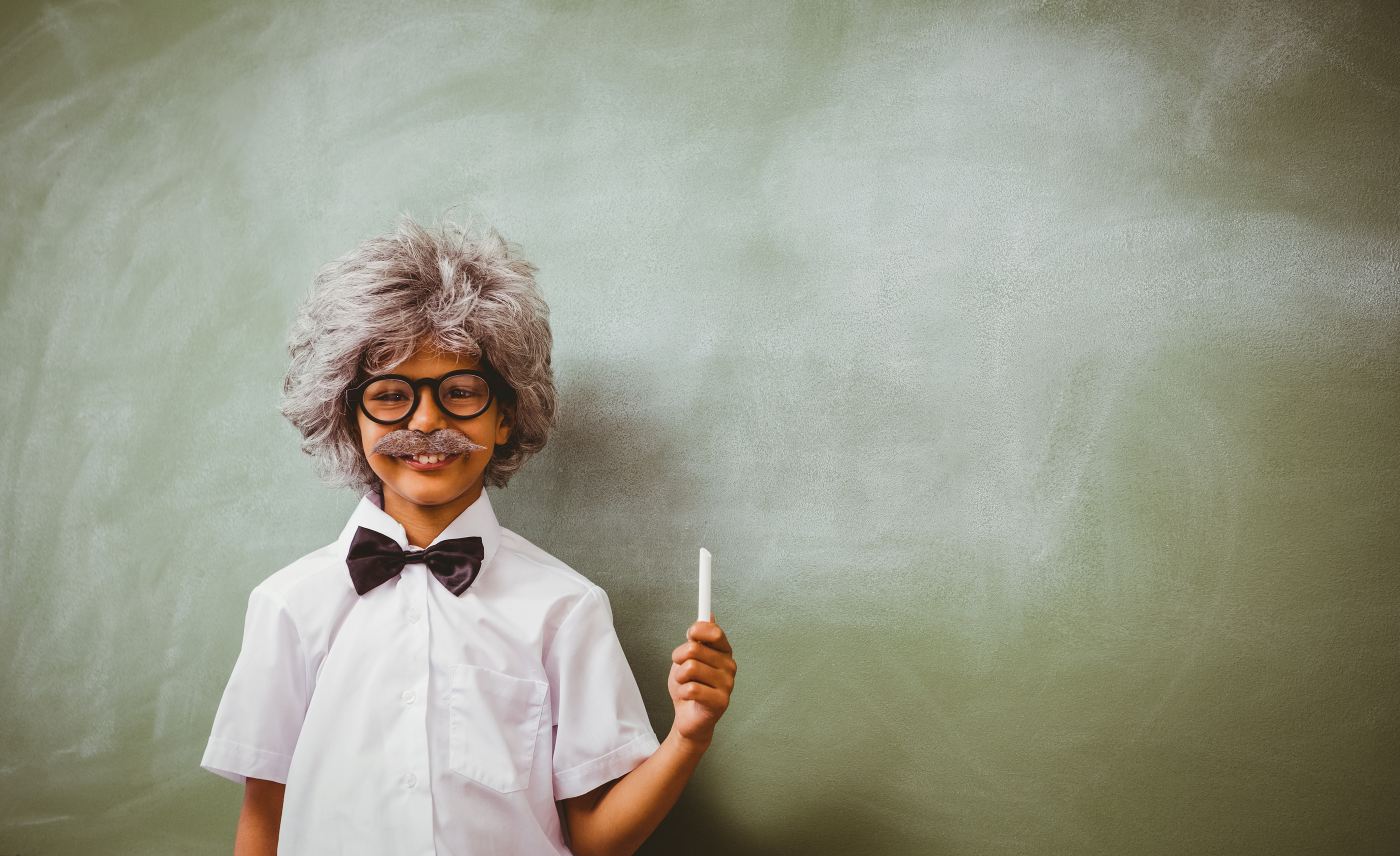 Portrait of little boy dressed as senior teacher in front of bla